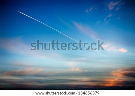 Track aircraft in the sky against the background of a beautiful sunset - stock photo