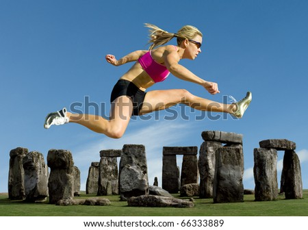 Track and field athlete hurdles over Stonehenge. - stock photo