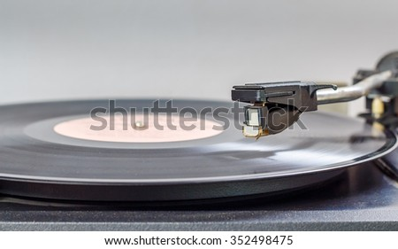 track from black vinyl. Turntable playing vinyl close up with needle on the record - stock photo