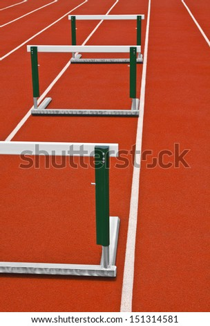 Track hurdles on a white stripped track. - stock photo