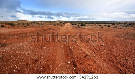 Track in the Australian outback, outside Broken Hill in western New South Wales.  A storm was brewing. - stock photo