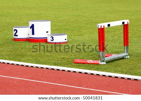 Track lanes with winner's podium and hurdles on green grass - stock photo