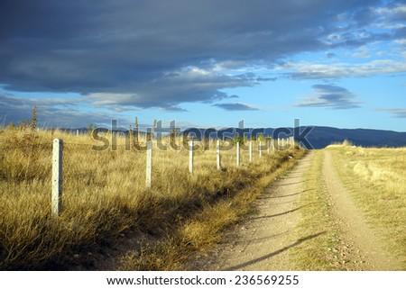 Track near fence and farmland in Turkey                                - stock photo