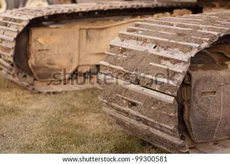 track of an excavator sitting on grass with dirt in the tracks - stock photo