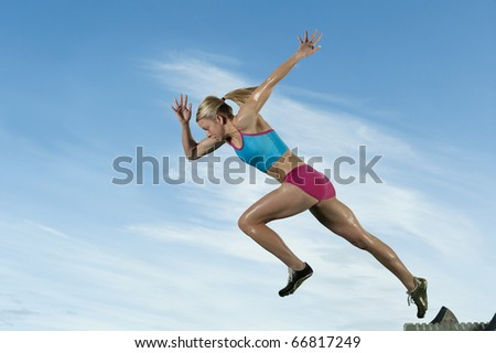Track runner bursts off starting block against a blue sky. - stock photo