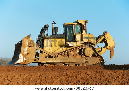 track-type bulldozer machine doing earthmoving work at sand quarry - stock photo