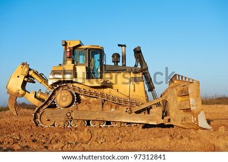 track-type bulldozer machine doing earthmoving work at sand quarry - stock photo