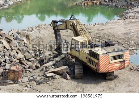 Track-type loader excavator machine doing earth-moving work at basalt quarry - stock photo