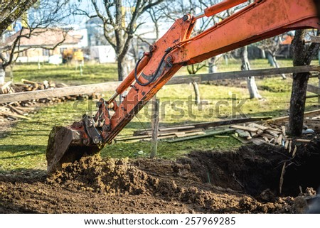 Track-type loader excavator machinery doing earthmoving and leveling at earth quarry - stock photo
