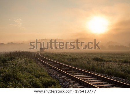 Track with the train in misty landscape at sunrise