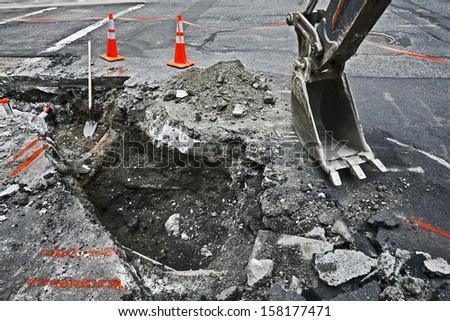 Tracked excavator on the street asphalt road repair - stock photo
