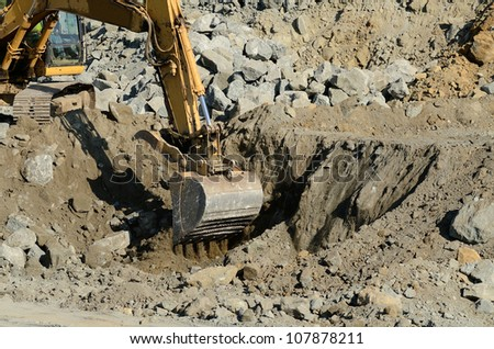 Tracked excavator or track hoe digging at a large construction site removing a hill during an airport runway expansion project