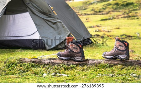 Tracking shoes in front of the tent on the green grass background - stock photo