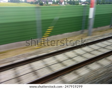tracks and rails out in motion from a moving train. symbolic photo for train, tempo and dynamics - stock photo