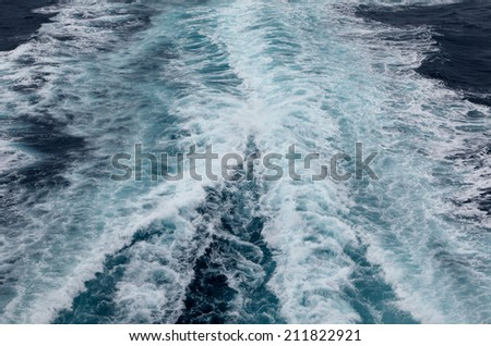 Tracks in the sea behind the cruise ship with dramatic sky - stock photo