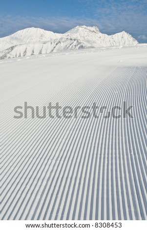 Tracks made by a snow grooming machine on a ski slope in the Alps. - stock photo