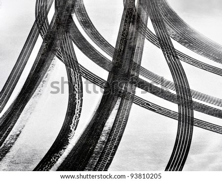 Tracks of car tires in thin layer of first snow - stock photo