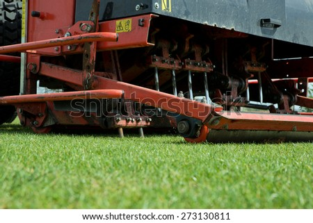 Tractor aerating a football field.