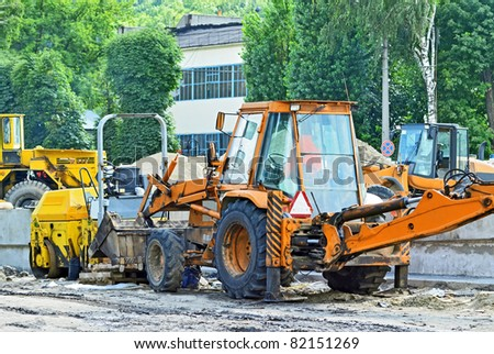 Tractor and asphalt paver on road construction site