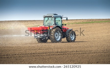 Tractor and fertilizer spreader in field