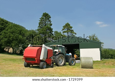 Tractor and hay baler standing in a field in summer next to an agricultural barn with one circular hay bale in view. Set against a blue sky with trees to the rear. - stock photo
