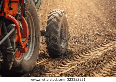 Tractor at work in the fields during a sunny summer day and tracks on the fertile soil - stock photo