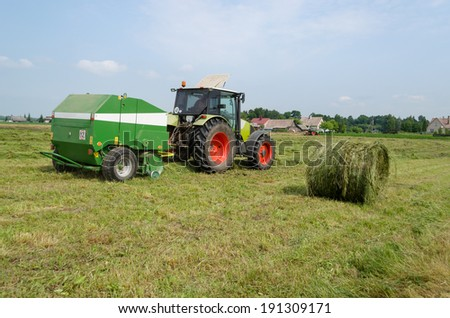 tractor bailer collect hay in field. Agricultural machine making hay bales. Seasonal rural works.  - stock photo