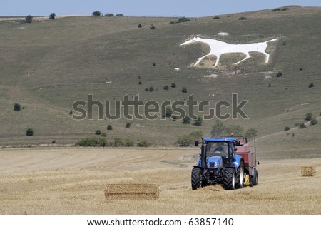 Tractor baling hay in field under White horse carved out of chalk hillside on Pewsey Downs at Alton near Avebury. Wiltshire. England. With heat haze. - stock photo