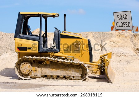 Tractor bulldozer which is being used to flatten area for new road. The earth has been pushed into a pile by the little bulldozer. - stock photo