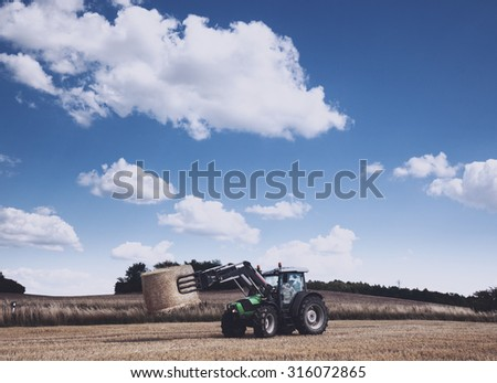 Tractor carrying hay at the field