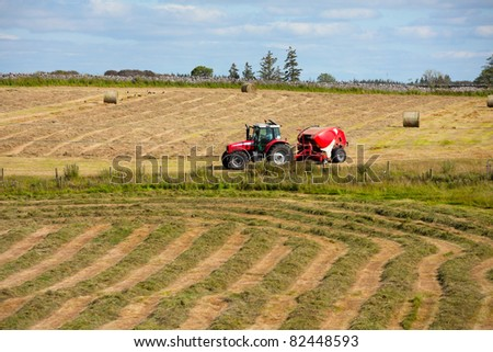 tractor collecting haystack in the field at nice blue sunny day, Ireland - stock photo