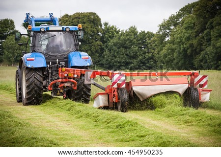 Tractor cutting grass hay with harvesting machine in the field