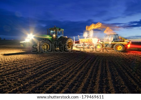 Tractor fall during the loading of grain for sowing - stock photo