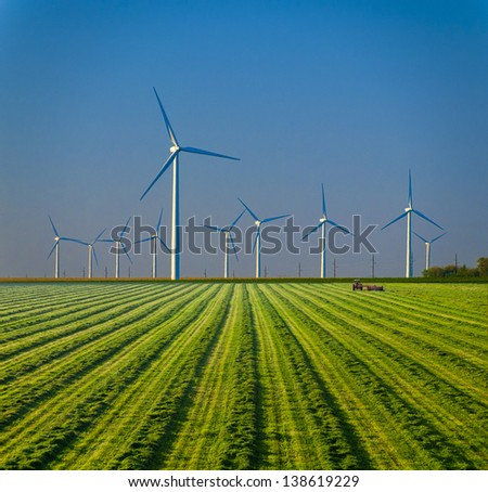 Tractor farming a green field under large wind turbines. - stock photo