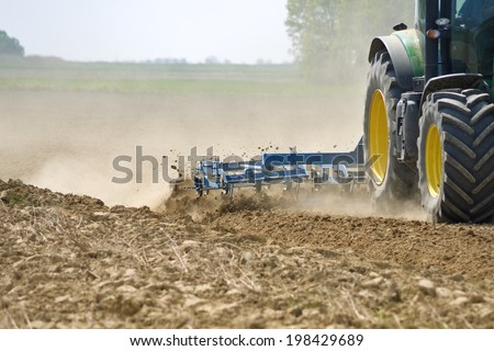 Tractor harrowing detail - stock photo