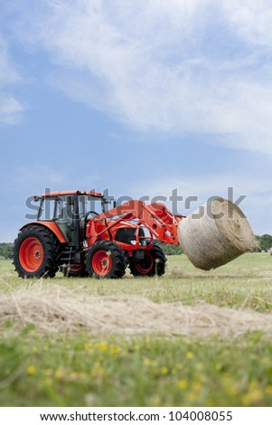 Tractor hauling a round bale an open field with blue sky. - stock photo