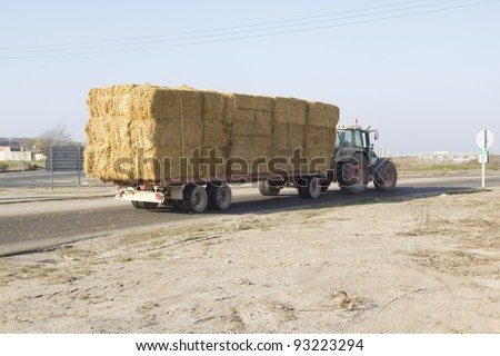Tractor hauling bales of hay for animal feed - stock photo