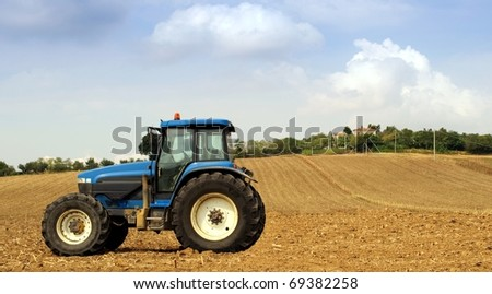Tractor in a field, agricultural scene in summer - stock photo