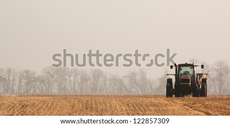 Tractor_in_Fieild_on_Foggy_Morning - stock photo