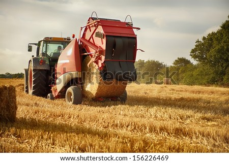 tractor in field throwing out hay roll - stock photo