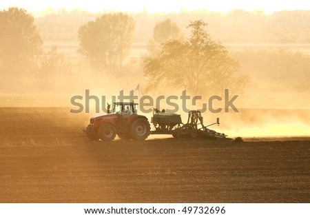 Tractor in sunrise plowing the field - stock photo