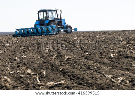 tractor in the field at planting - stock photo