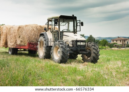 Tractor loaded with hay and farm house in the background, Italy