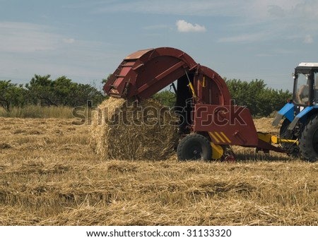 Tractor making straw rolls. Agriculture concept - stock photo