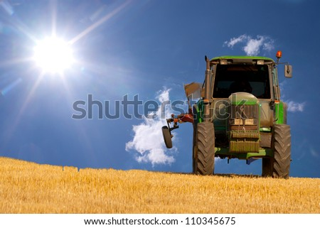 Tractor on a field with blue sky and sun as background - stock photo
