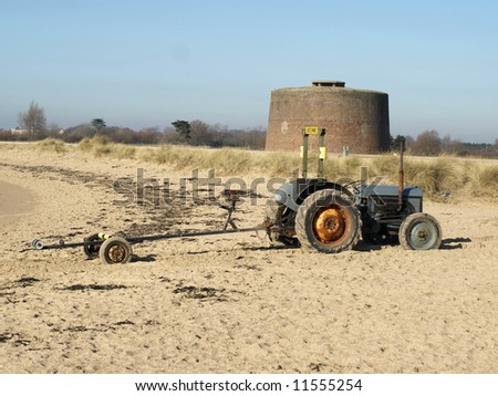 Tractor on a sandy beach with a round fort - stock photo