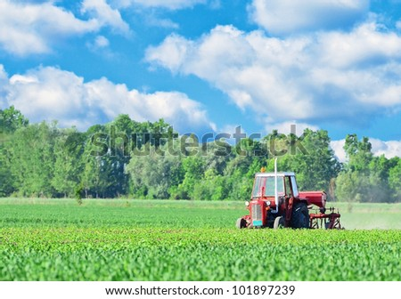 Tractor on beautiful landscape - stock photo