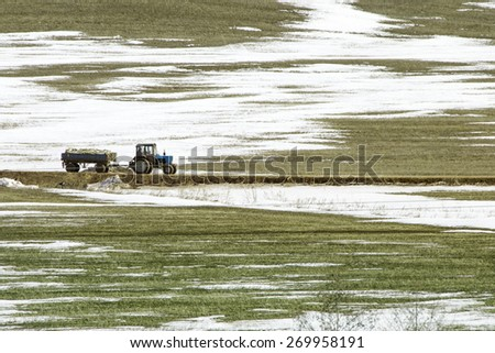 Tractor on snowy field - stock photo