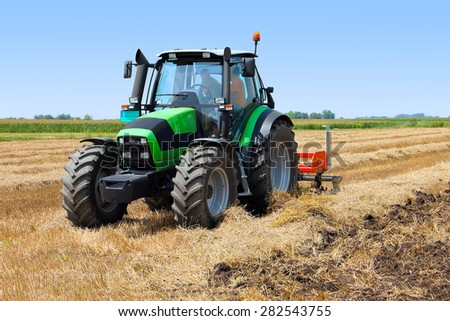 Tractor on the farmland - stock photo