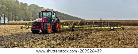 tractor on the field with shirokozahvatnymi Tine Harrow - stock photo